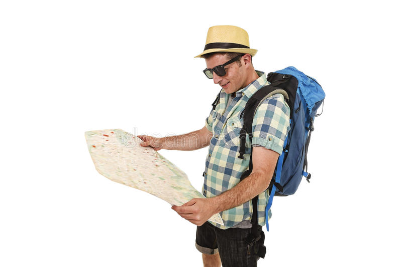 Young tourist man reading city map looking relaxed and happy carrying backpack wearing summer hat royalty free stock photos