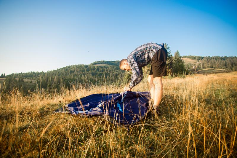 Young tourist man setting up tent on autumn meadow, traveling high in mountains royalty free stock photo
