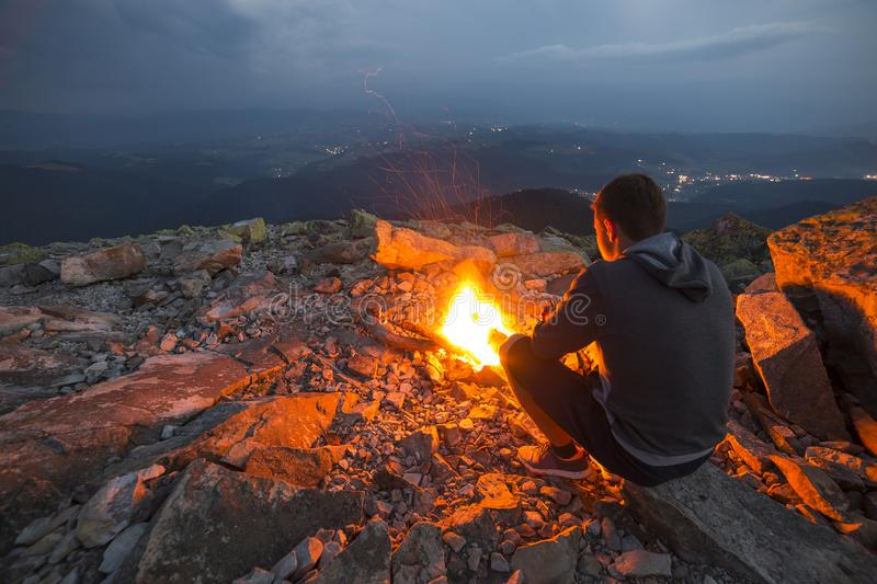 Young tourist man sitting on summer night at bright fire on rocky mountain top under cloudy sky. Young tourist man hiker sitting on summer night at bright fire stock photos