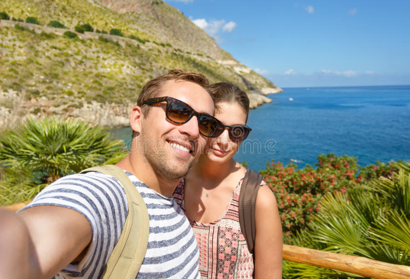 Young tourist take a selfie memory photo in tropical scenery during vacation around Italian coasts. Smiling couple. royalty free stock photography