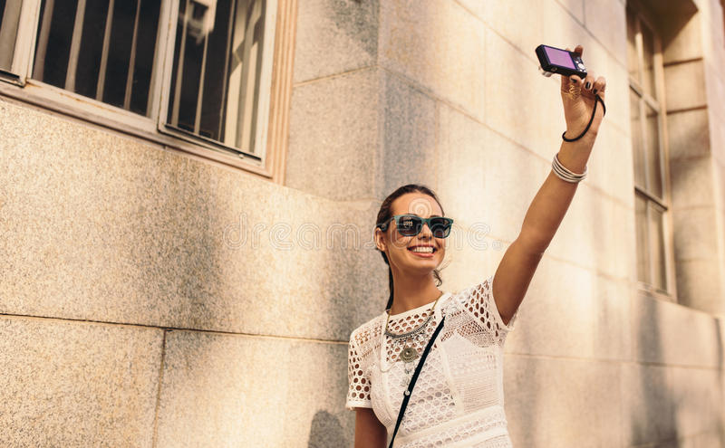 Young tourist taking a selfie in the street. Stylish young woman taking selfie in a street using a digital camera. Fashion vlogger recording content for her stock image