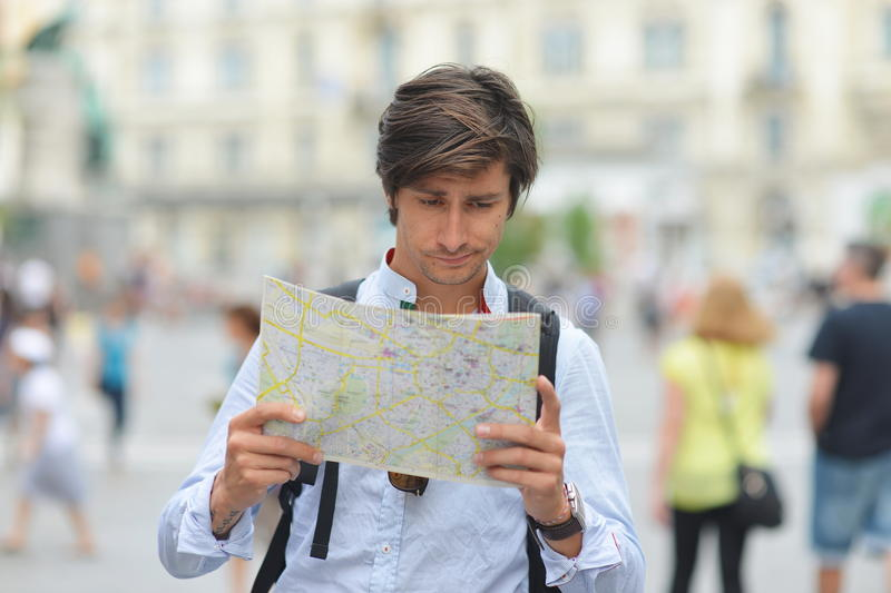 Young tourist watching the map stock photography