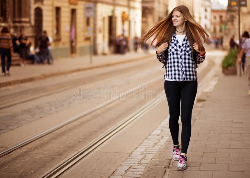 Young tourist woman with backpack walk by street in old europe city, summer fashion style stock images