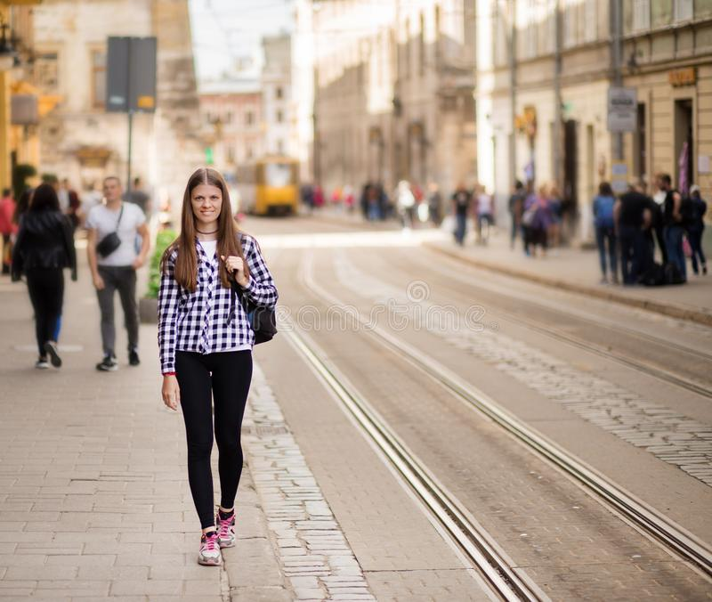 Young tourist woman with backpack walk by street in old europe city, summer fashion style royalty free stock photo