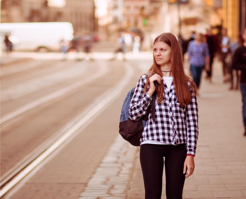 Young tourist woman with backpack walk by street in old europe city, summer fashion style royalty free stock images