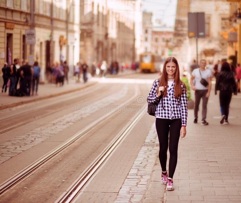 Young tourist woman with backpack walk by street in old europe city, summer fashion style stock photography