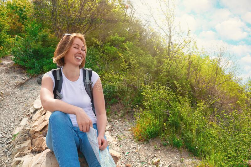 A young tourist woman climbed the mountain , and at the top decided to relax a little. Plants and sky with clouds on the. Background. Sun light stock photo