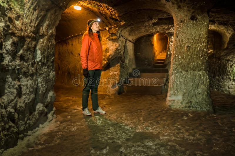 Young tourist woman explore ancient Derinkuyu underground cave city stock image