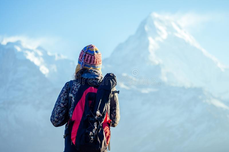 A young tourist woman with a hiking backpack and a knitted hat in the Himalaya mountains. trekking concept in the royalty free stock photography