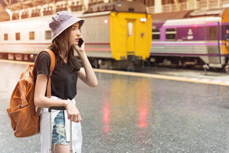 Young tourist woman holding cellphone and call Find accommodation on railway station. Travel concept royalty free stock photography