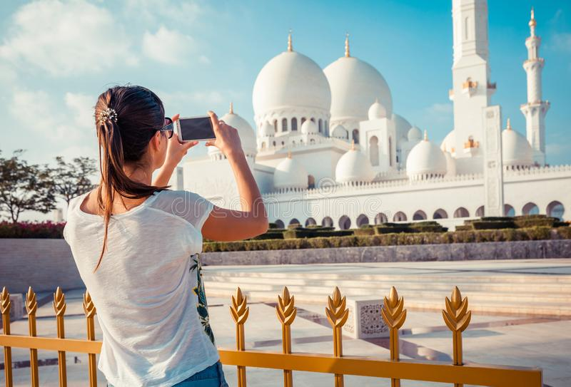 Young tourist woman shooting on mobile phone Sheikh Zayed great white mosque in Abu Dhabi, United Arab Emirates, Persian gulf. UAE. Young tourist woman shooting royalty free stock images
