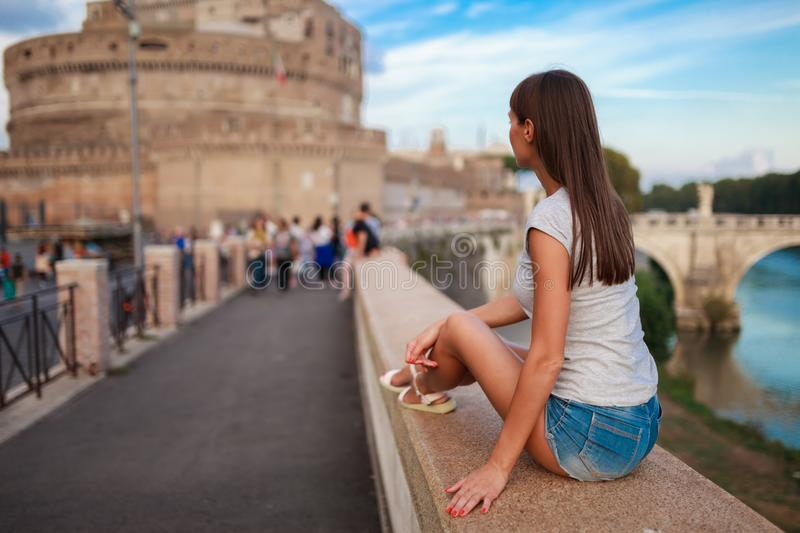 Young tourist woman sitting on the ancient embankment Tiber in Roma at sunset. Near of bridge and castle of Angels. Saint Angelo stock images