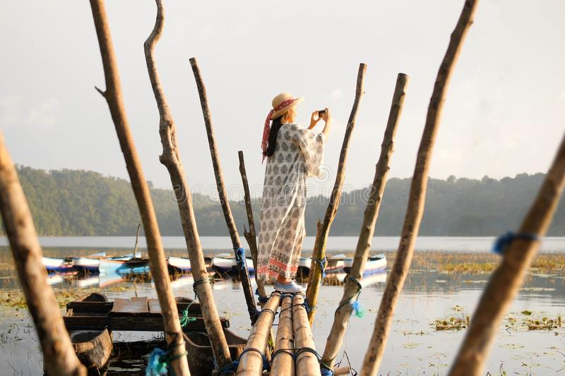 Young Tourist Woman in Straw Hat and White Dress Standing on Wooden Pier and Taking Photos of Beautiful Morning View on Lake and royalty free stock image