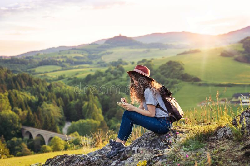 Young tourist woman traveller with backpack sitting in nature, writing notes. stock images