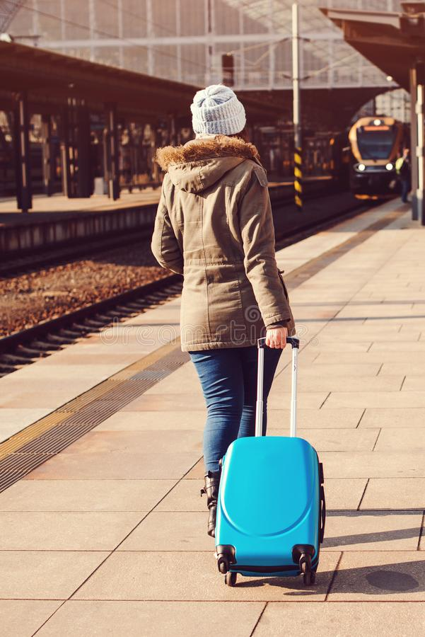 Young tourist woman walking, dragging luggage suitcase bag. Girl at railway station. Journey concept. Lifestyle, travelling, vacat stock photo