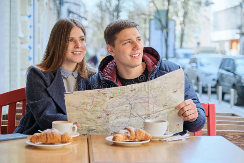 Young tourists man and woman reading map of city in outdoor cafe. Couple drinking coffee tea and eating croissants, spring city royalty free stock photography