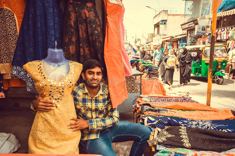 Young trader working with female fashion in textile store of busy market street royalty free stock photography