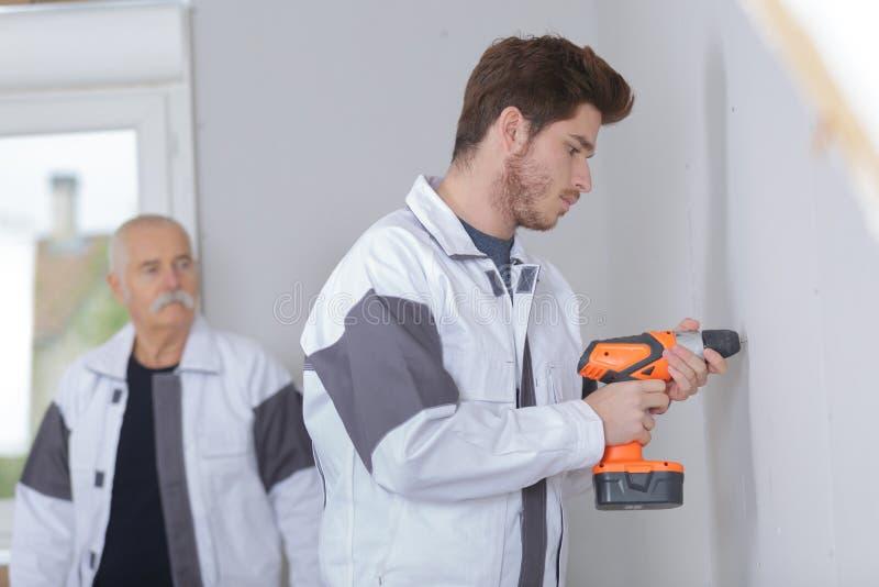 Young tradesman using cordless drill royalty free stock image