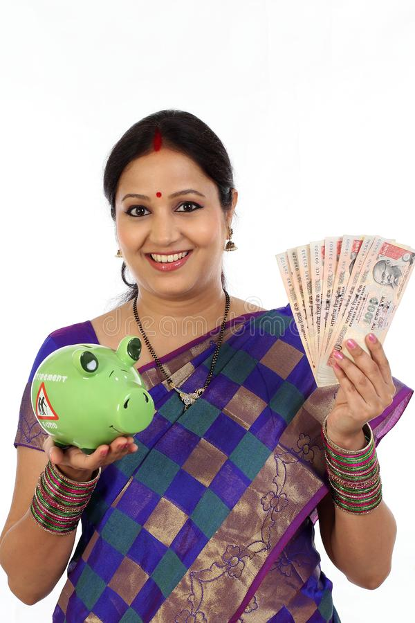 Young traditional woman holding Indian currency and piggy bank royalty free stock image