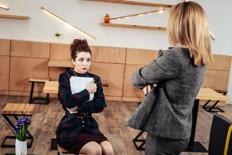 Young trainee feeling worried listening to her strict female boss royalty free stock photo