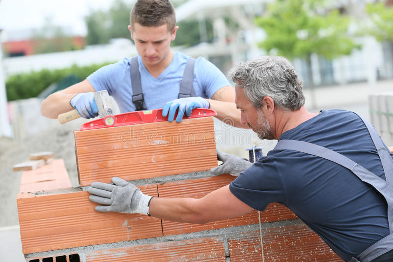 Young trainee learning masonry with instructor. Mason with trainee in construction, building wall royalty free stock photos
