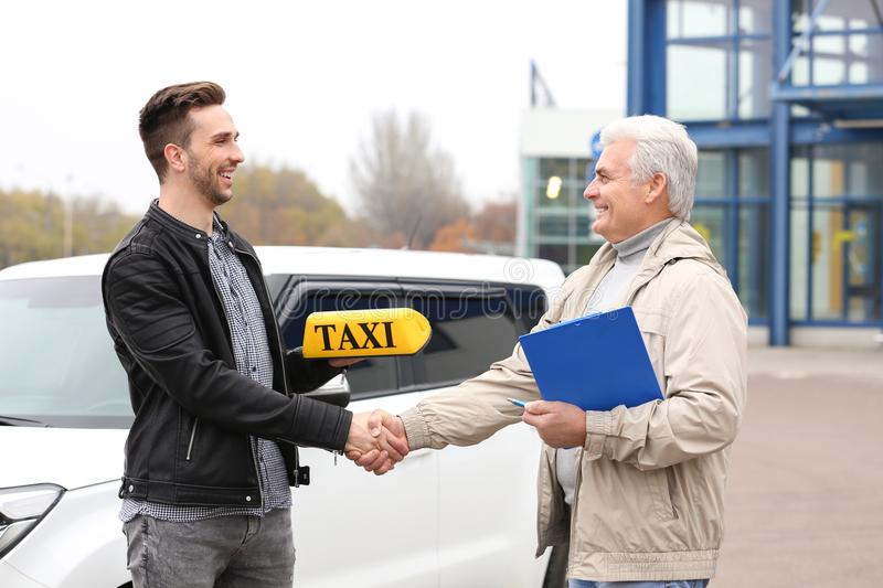Young trainee shaking hands with senior taxi driver stock image