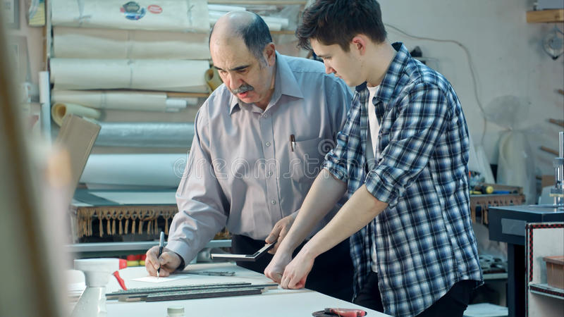 Young trainee studying how to construct a frame, senior worker talking to him behind the desk in frame workshop. Professional shot in 4K resolution. 083. You stock image