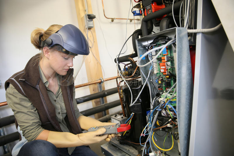 Young trainee verifying electronical installation stock photography