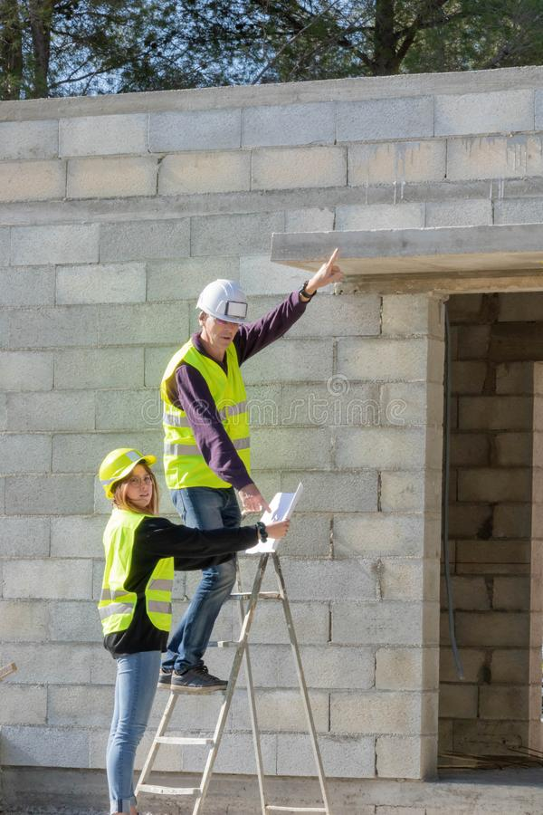Young trainee woman with her tutor on a construction site visit, building trades. Construction site house, construction site visit, construction industry royalty free stock image