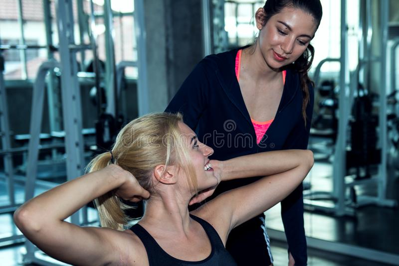 Beautiful trainer advise a young woman for exercise at the gym stock photography
