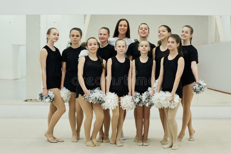 Young Trainer mit Team von Cheerleader Girls stockbild