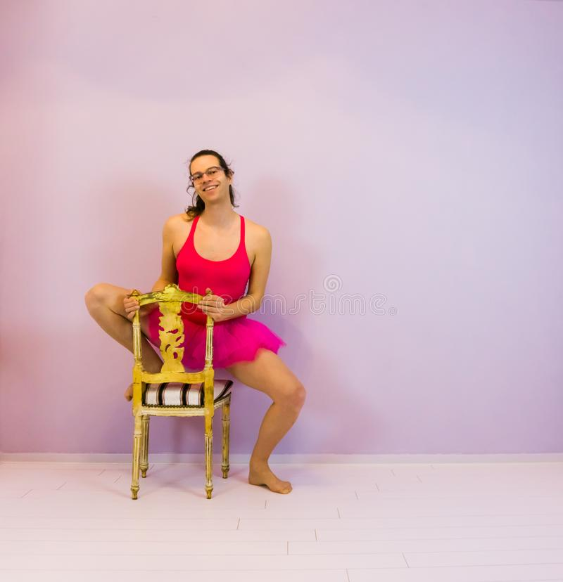 Young transgender ballet dancing girl posing on a chair, LGBT portrait in the sport stock image