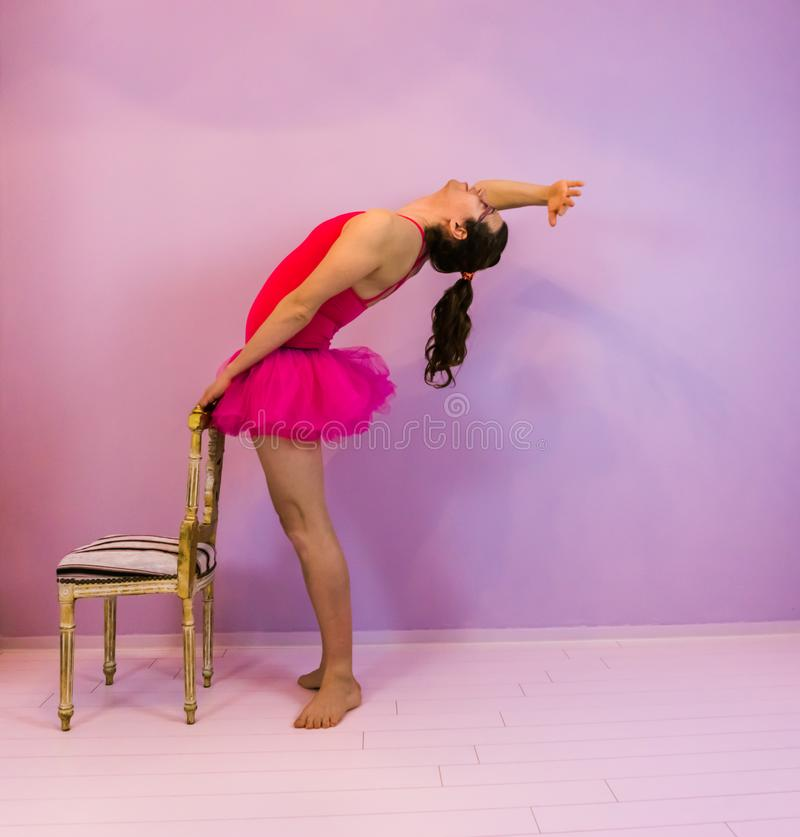 Young transgender girl performing a back cambre in a pink tutu, LGBT in the dancing sport royalty free stock images