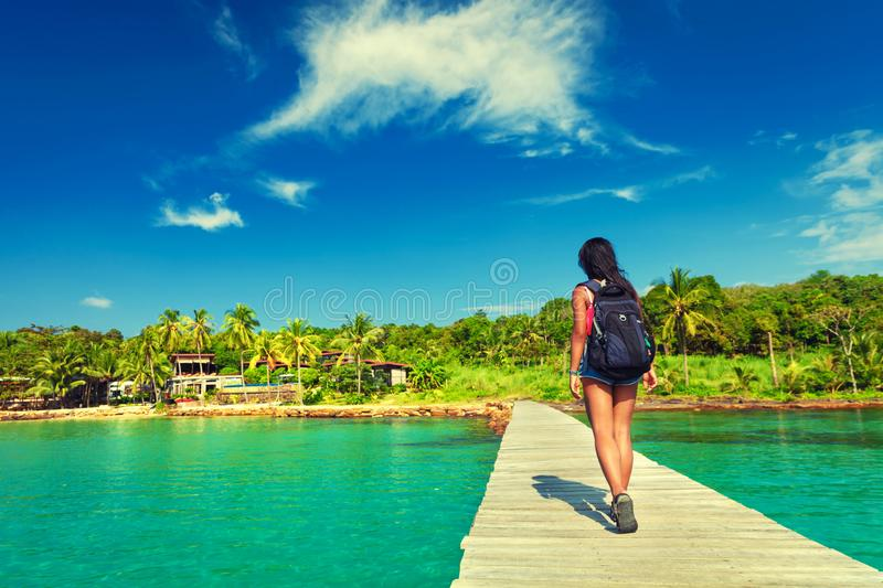 Young travel girl backpacker walks with backpack along a scenery wooden bridge to a tropical paradise island stock photo