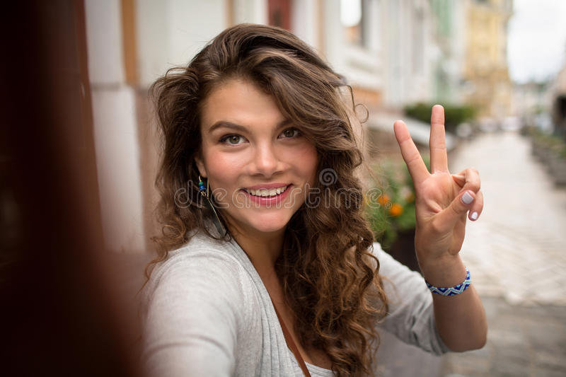 Young travel girl, having fun showing fingers on selfie photo. stock photo
