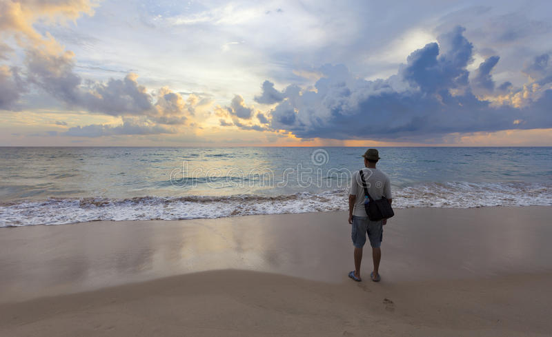 young travel man standing alone on the beach and looks at the sunset in phang-nga thailand. stock photos