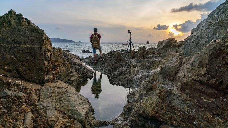 Young travel man standing on rocks with Dramatic sky and wave seascape in sunset scenery background royalty free stock photography
