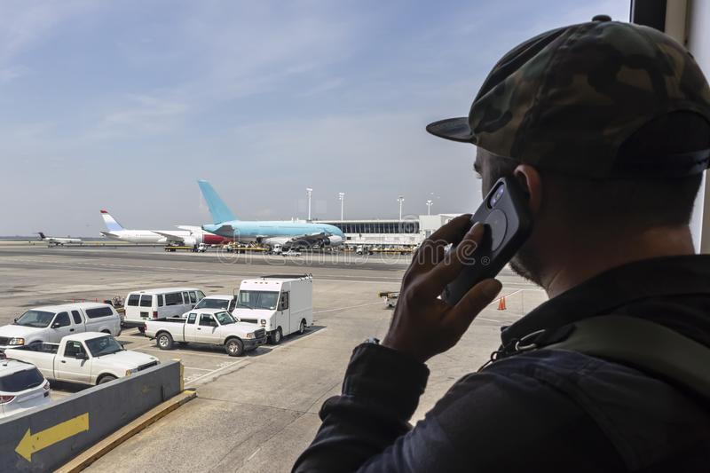 Airport Traveler Calls Law Enforcement After Seeing Terrorist Ac. A young traveler calls law enforcement after seeing something suspicious at an international royalty free stock photography