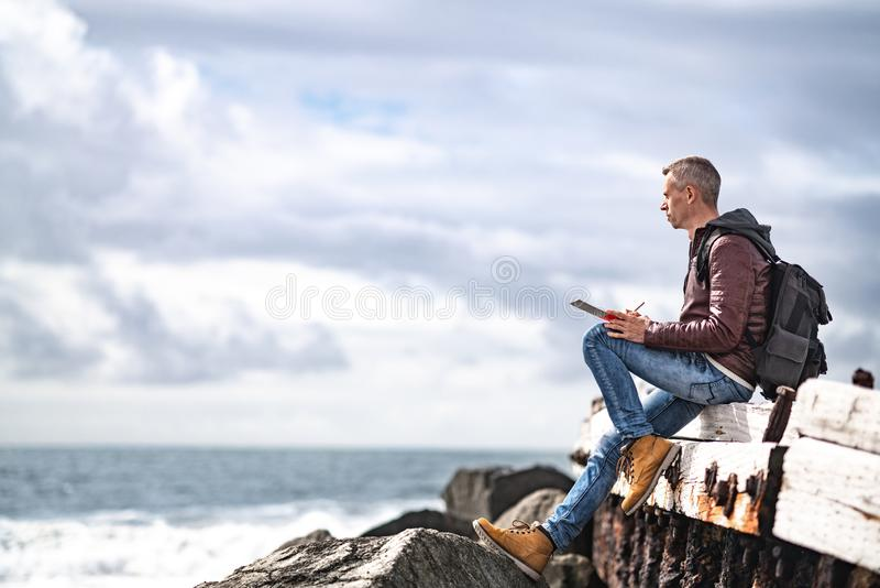 Young traveler with a camera by the ocean. California royalty free stock photography