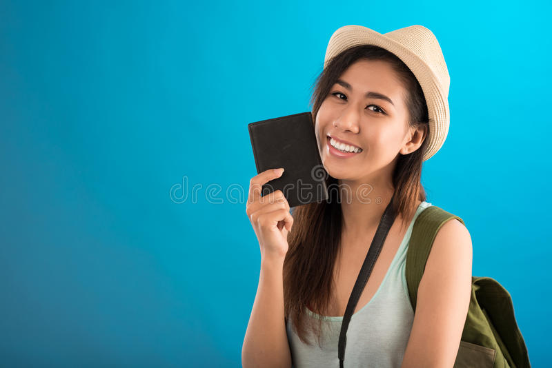 Young traveler. Copy-spaced portrait of a young female traveler with an international passport in hand smiling and looking at camera over a blue background stock photo