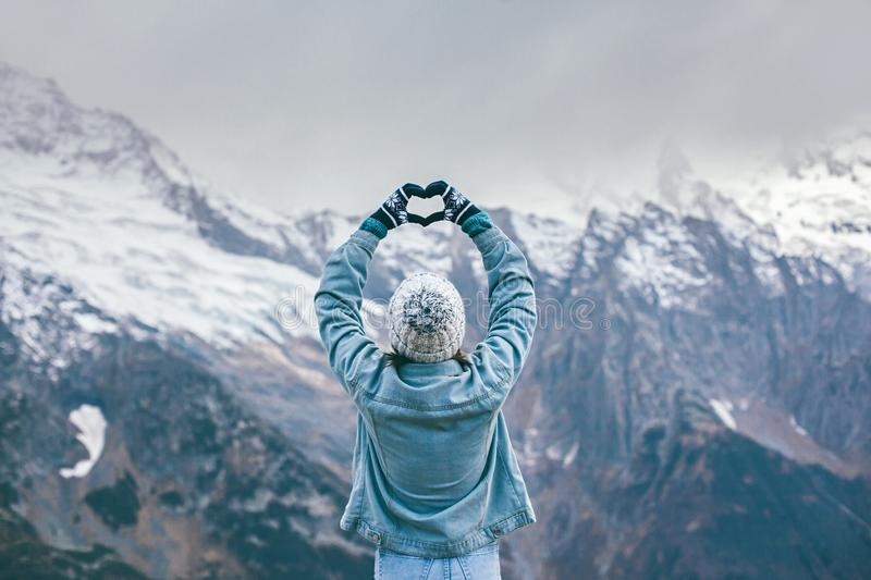 Young traveler girl in gloves standing over mountain peaks and making heart by hands royalty free stock image