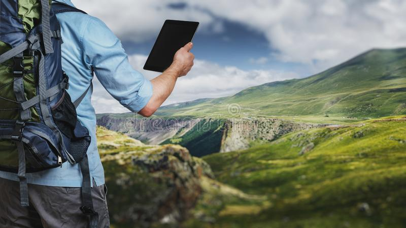 Young traveler hiker with backpack looking at the route map in a royalty free stock images