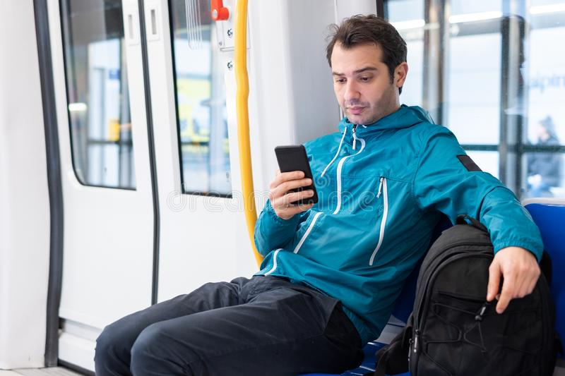 Young traveler reading social network on cell phone on subway metro public transport. Concept of commute connection communication social media royalty free stock photo