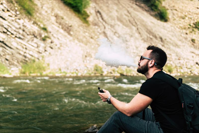 Young traveler smoke electronic cigarette near mountain river royalty free stock photo