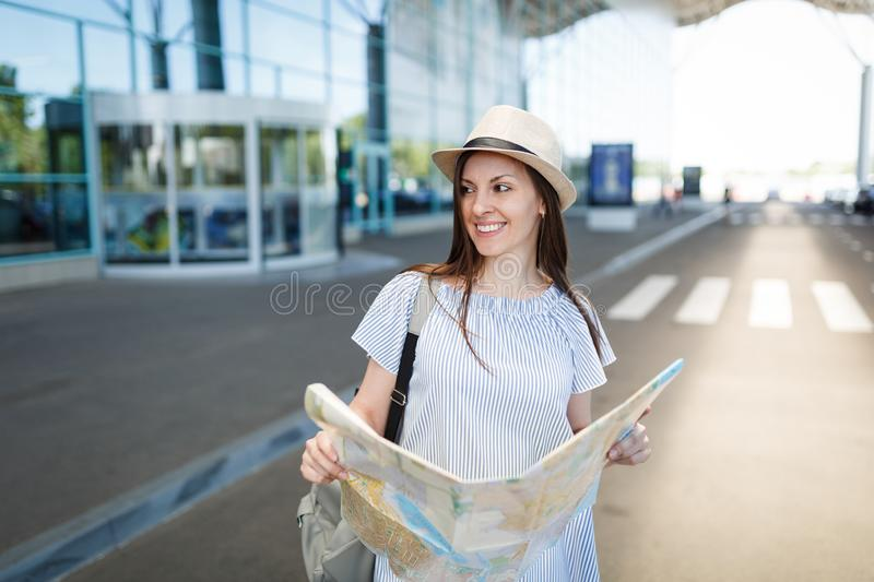 Young traveler tourist woman with backpack hold paper map, looking aside at international airport. Female passenger. Traveling abroad to travel on weekends stock photo