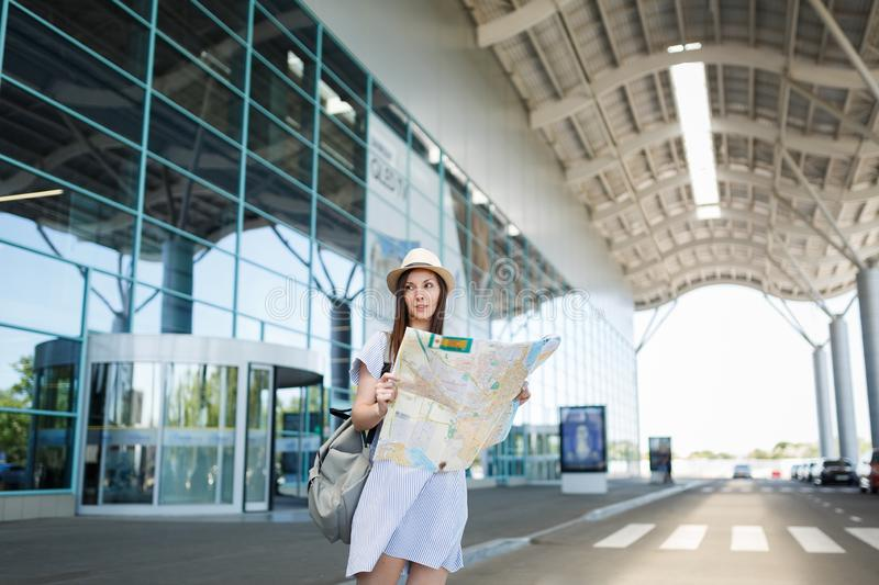 Young traveler tourist woman with backpack standing at international airport, holding paper map. Female passenger. Traveling abroad to travel on weekends stock photo