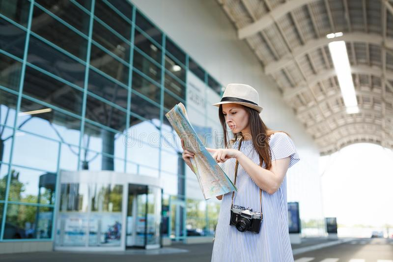 Young traveler tourist woman with retro vintage photo camera search route in paper map at international airport. Female stock images