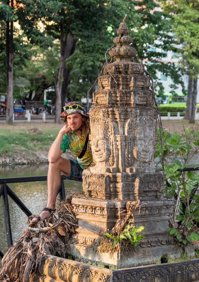 Young traveler wearing a hat with backpack and tripod - at Angkor Wat, Siem Reap, Cambodia royalty free stock image