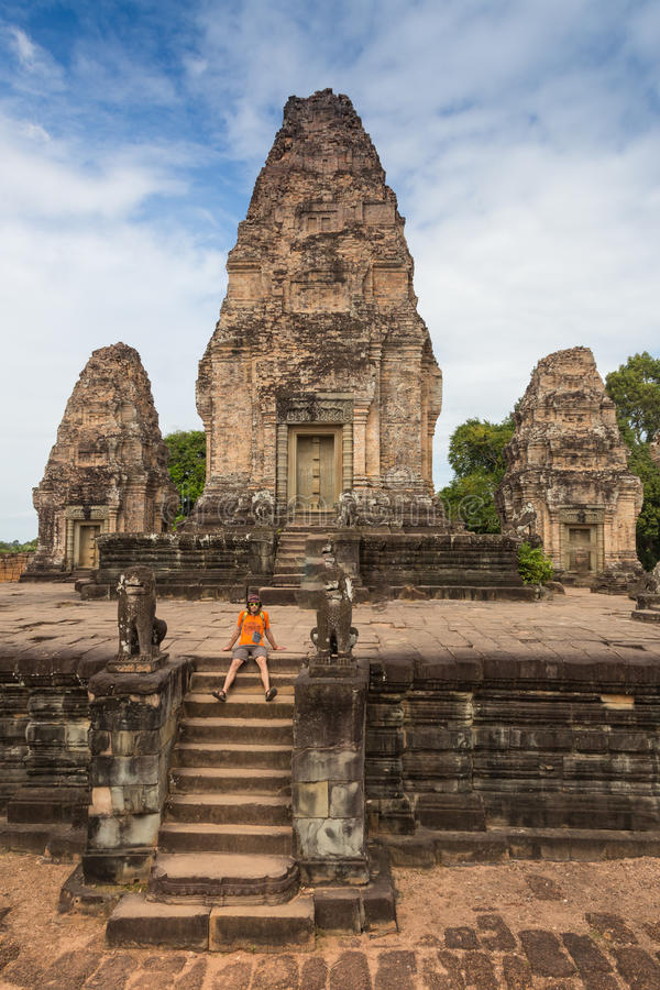 Young traveler wearing a hat with backpack and tripod - at Angkor Wat stock photo