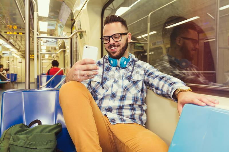 Young traveler wearing plaid shirt and glasses reading fun feeds on social network pages on cell phone on subway metro public royalty free stock photography